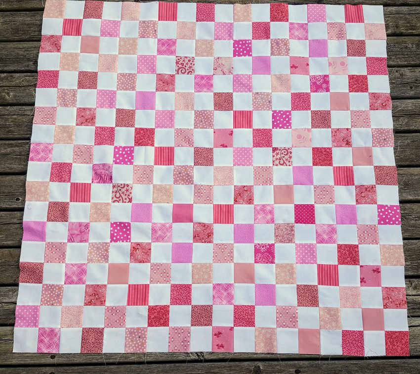 scrappy pink and white baby quilt top